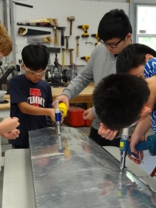 Teaching 5th graders how to rivet on an airplane part.
